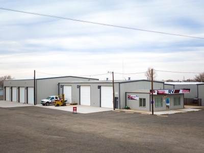 Long view of RV Pro primary building and RV yard, in Lubbock, Texas, illustrating RV bays and doors.